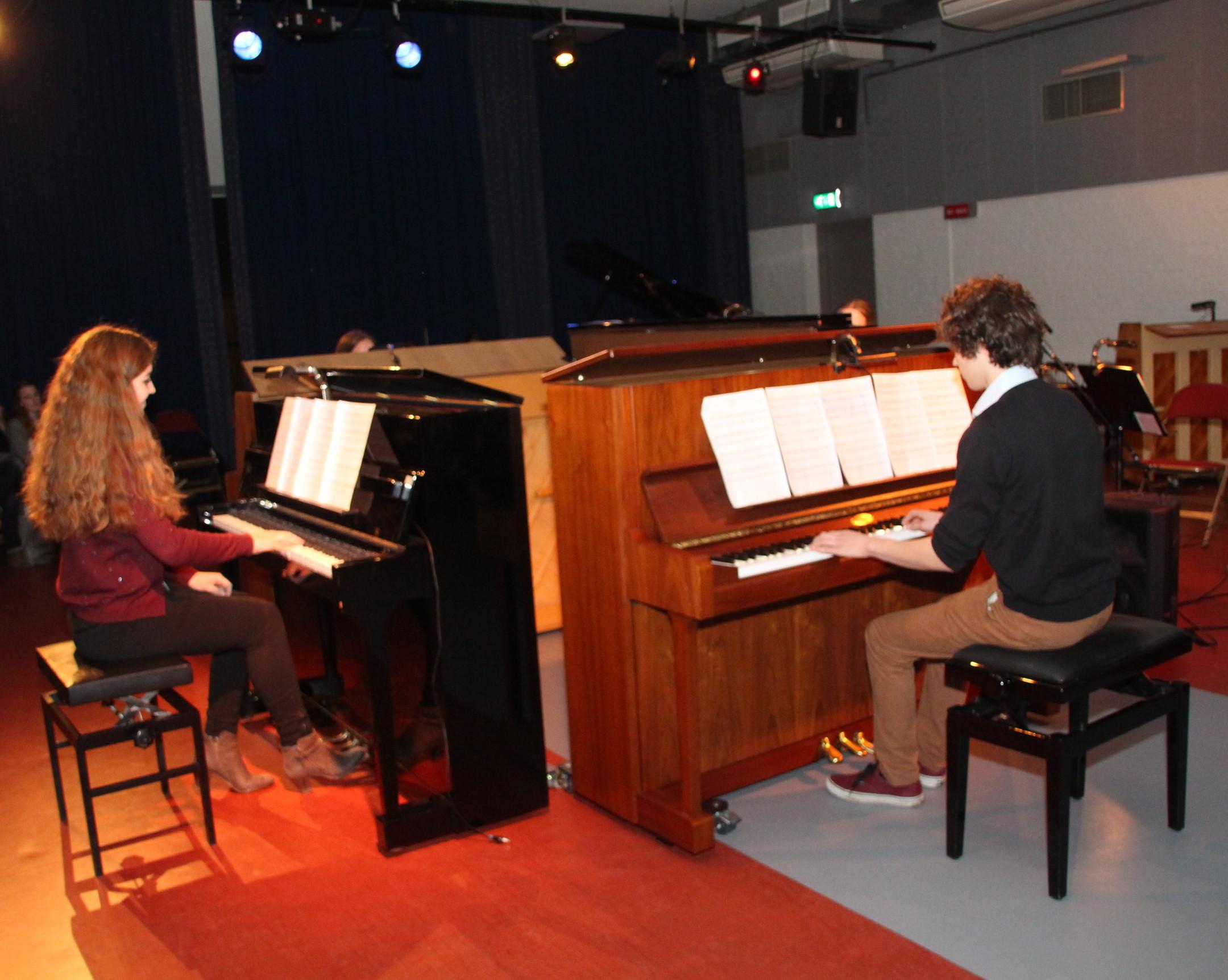Vier leerlingen spelen piano